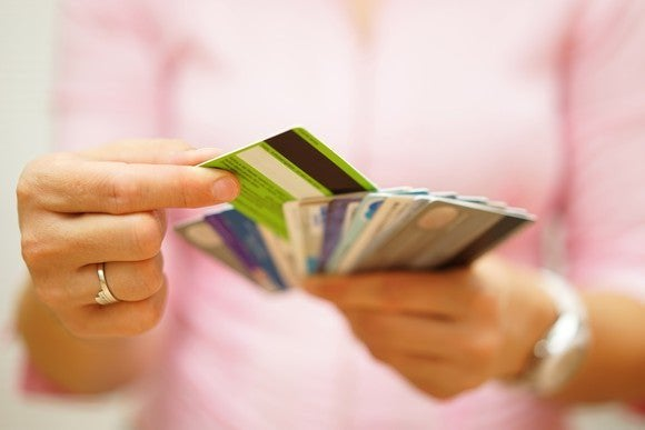 A woman holding multiple credit cards and selecting one.