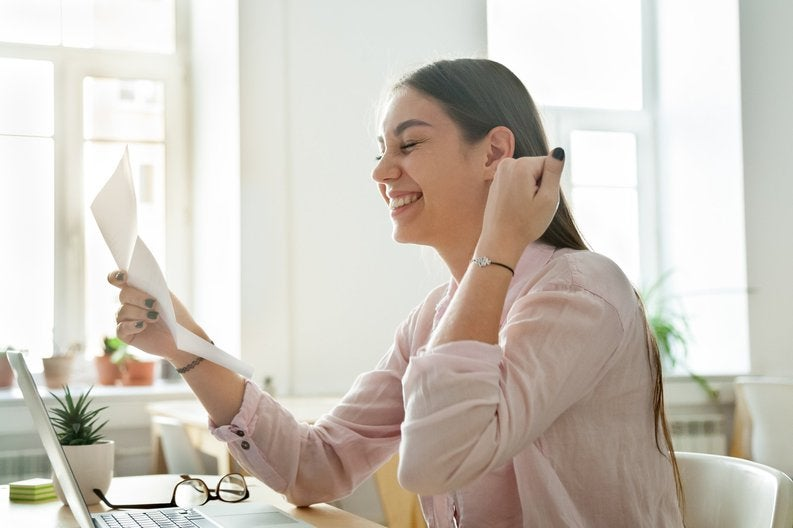 woman smiling and looking at paperwork