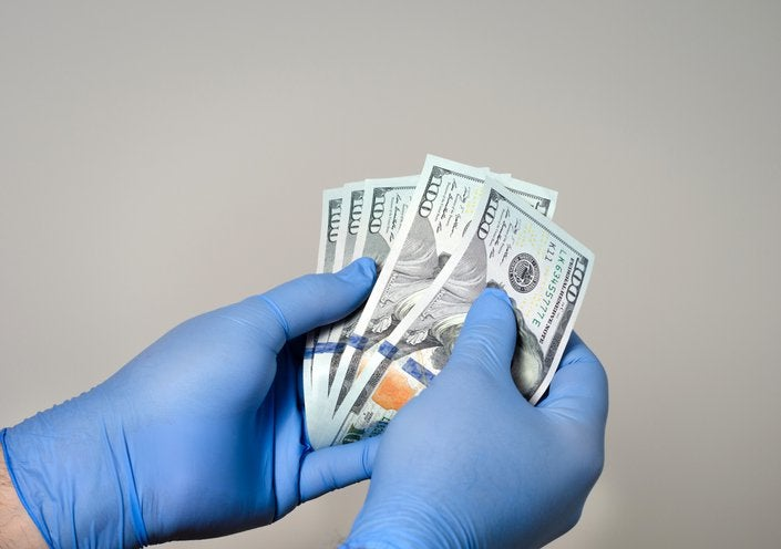 GLoved hands hold hundred-dollar bills.