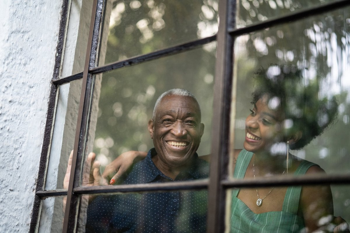 A smiling grandfather and his adult granddaughter looking out of window at the trees.