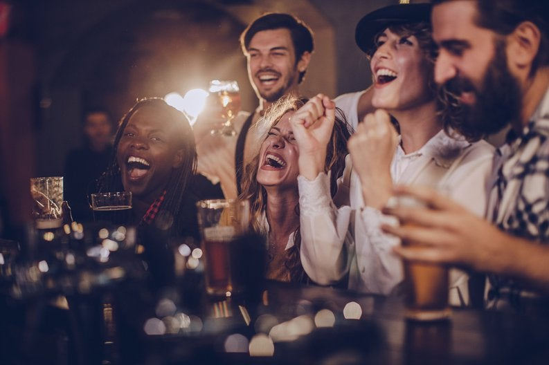 A group of friends laughing over drinks at a bar.
