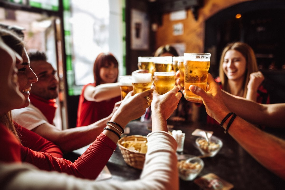 A group of friends cheersing their beers at happy hour.