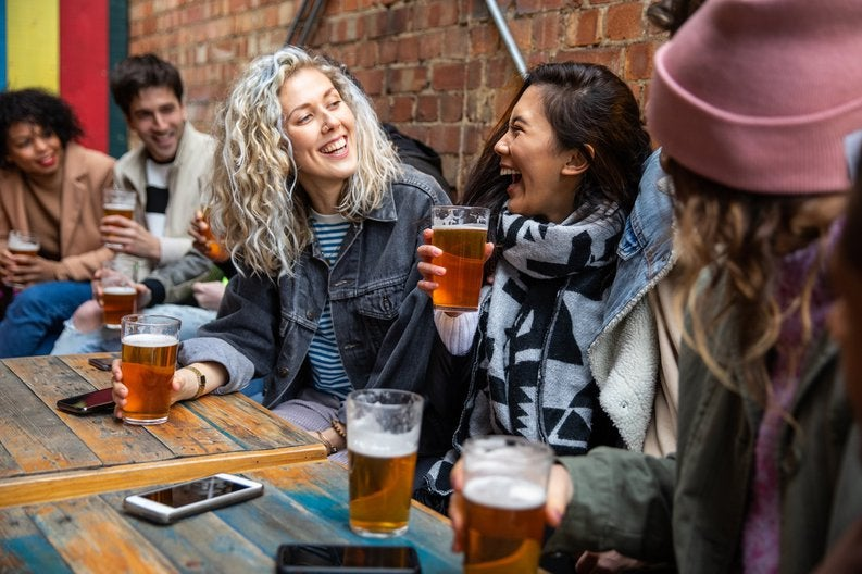 A group of friends drinking beer at a pub.
