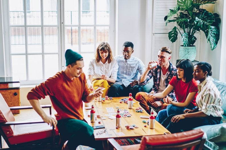 A group of friends sitting around a living room coffee table playing poker.