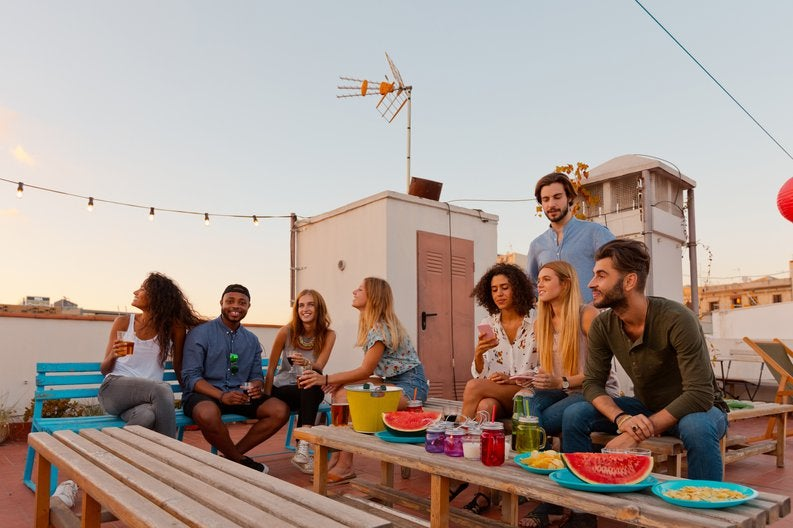 A group of young adult friends hanging out on a decorated rooftop with cocktails at dusk.