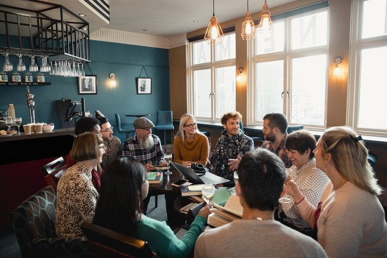 A group of people sitting in a circle of chairs having a social meeting at a restaurant.