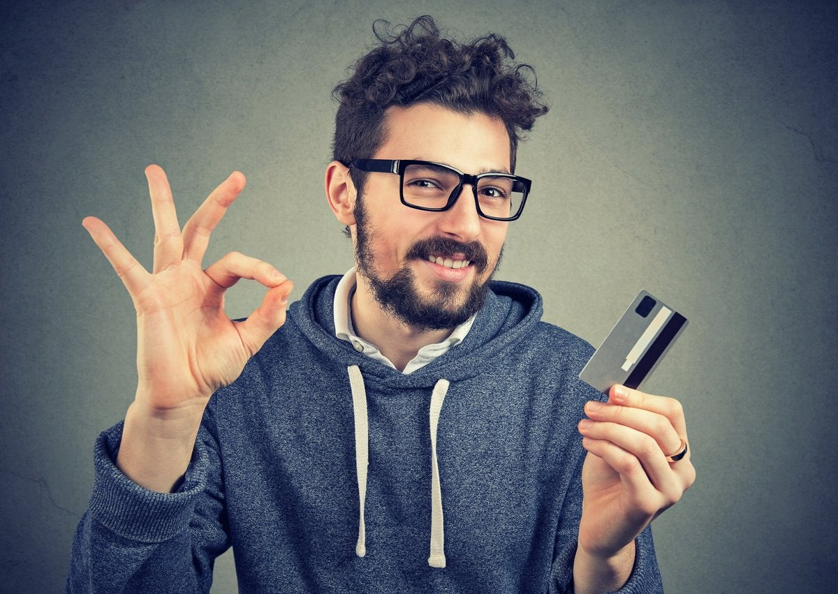Guy making OK sign holding credit card.