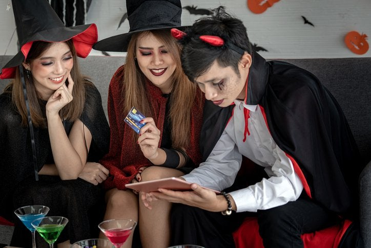 Two young women and a young man on a couch in Halloween costumes shopping with a laptop and a credit card.