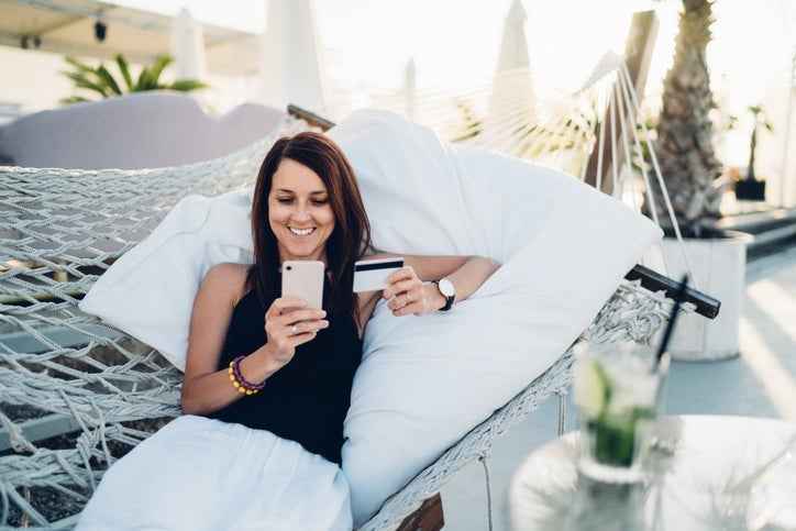 A woman in a hammock holding a phone and a credit card.