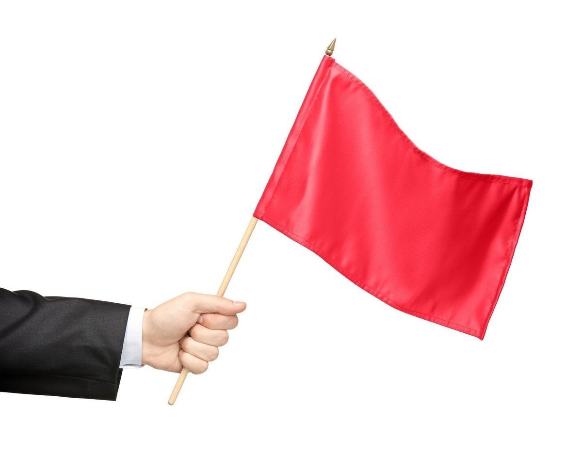 Hand holding out a red flag.