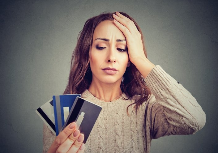 A woman looks at a handful of credit cards.