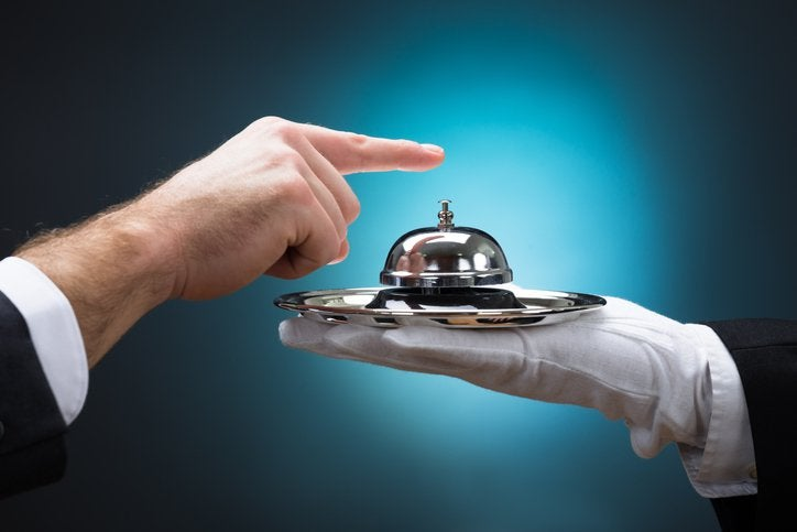 Someone rings a service bell held by a gloved hand
