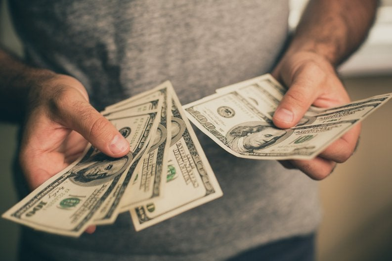 A man holding several hundred dollar bills in his hands,