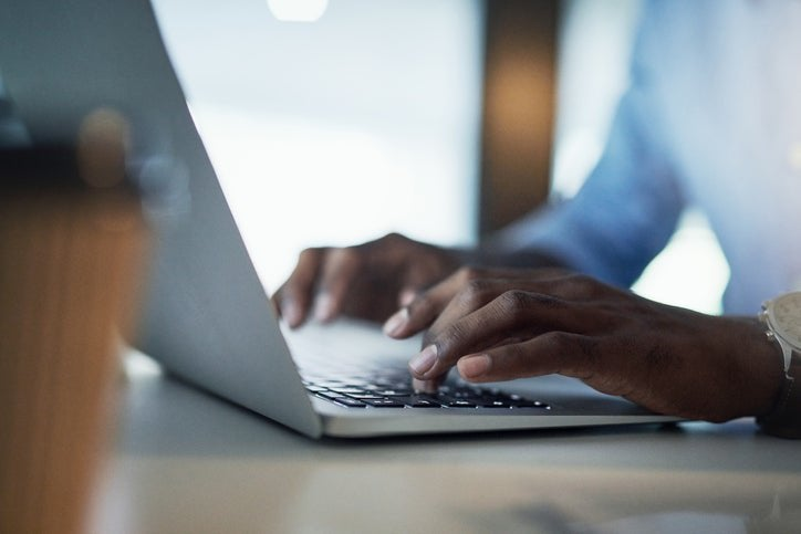 A man's hands typing on a laptop keyboard.