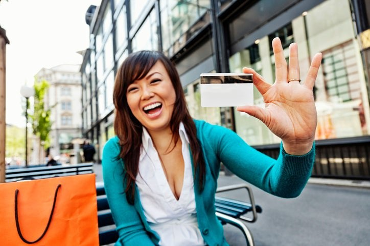 A smiling woman holds up a credit card.