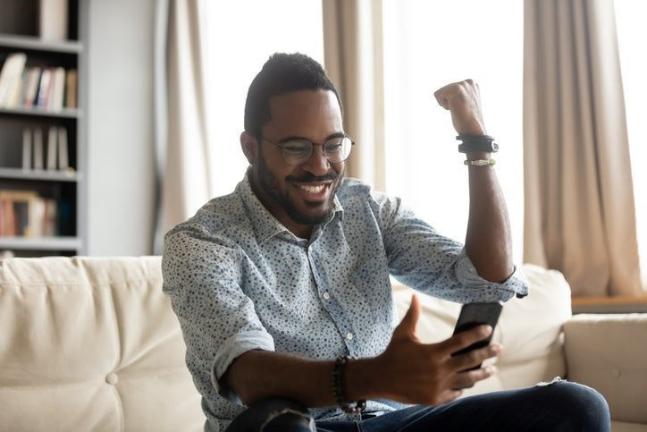 A man pumping his fist in excitement while sitting on his couch and looking at something on his phone.
