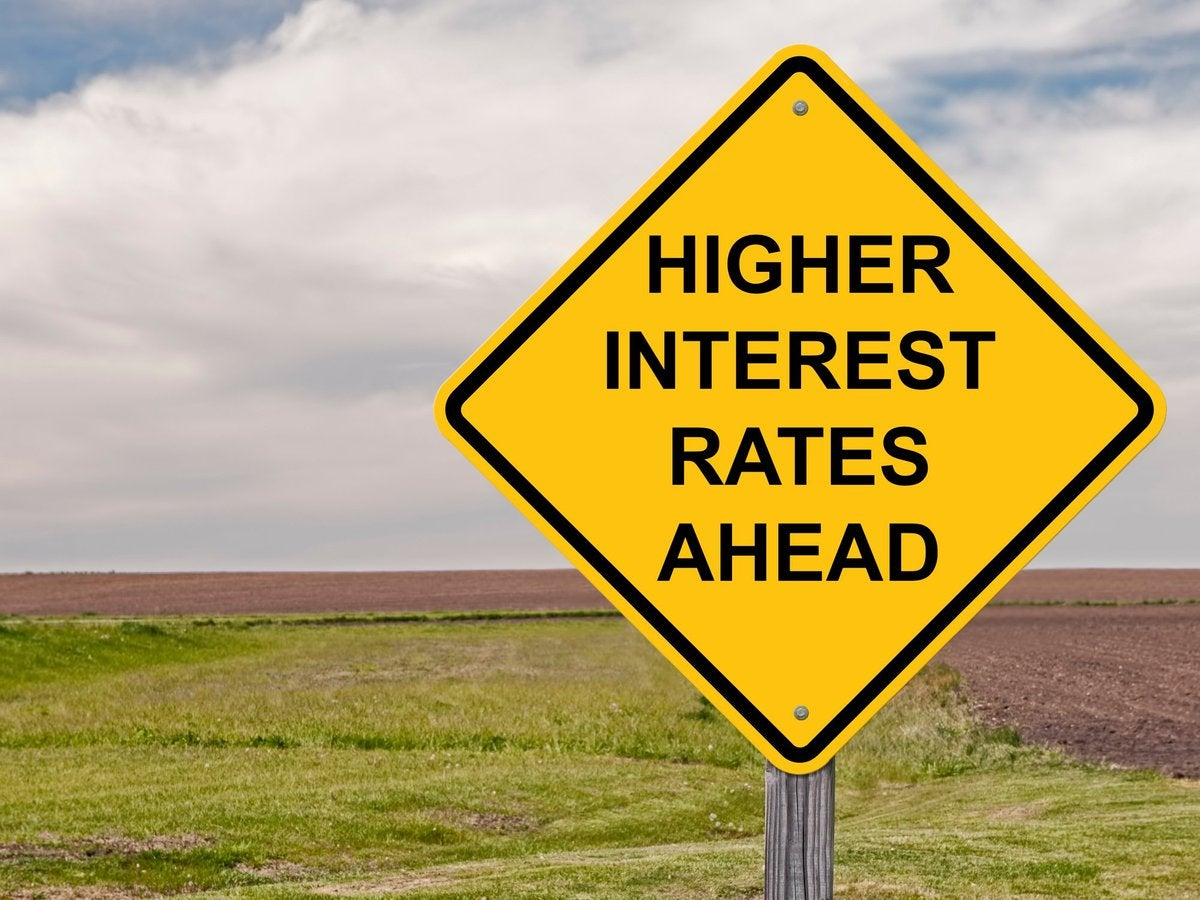 A yellow road sign reading Higher Interest Rates Ahead.