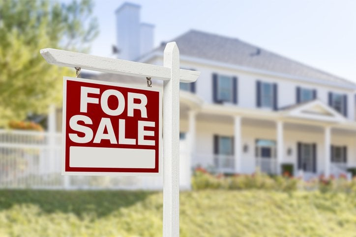 A For Sale sign in front of a sunny green lawn and white two-story home.