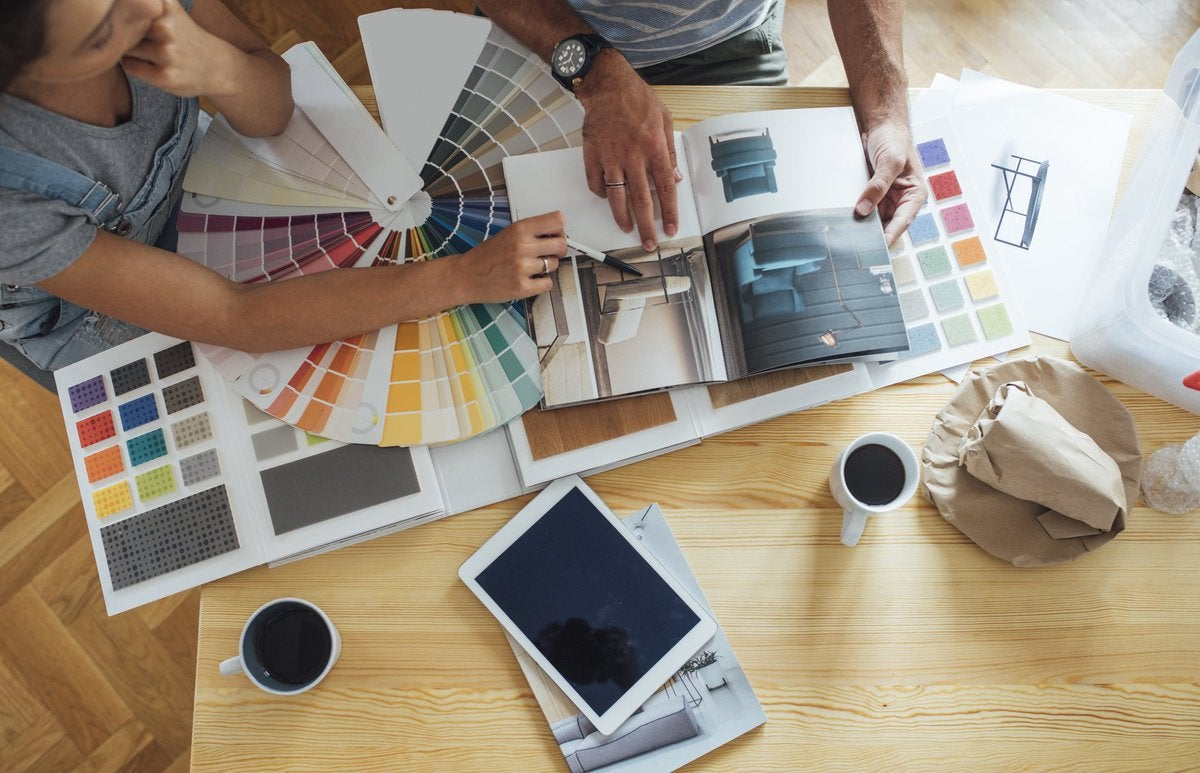 A couple looks over paint colors and a home decor magazine.