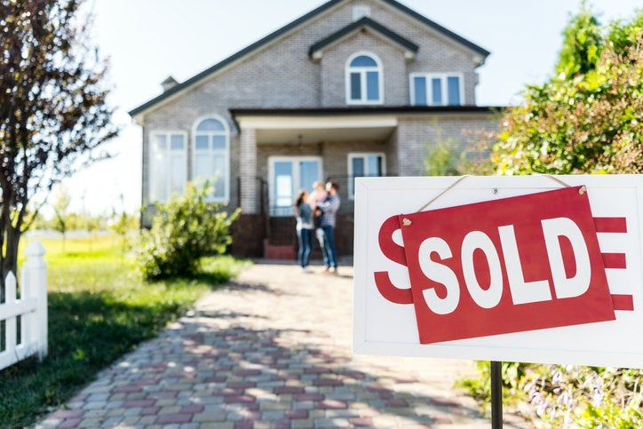 A Sold sign in front of a driveway leading up to a family standing in front of their new home.