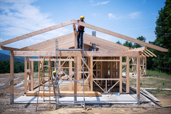 The frame of a house under construction with workers on site.
