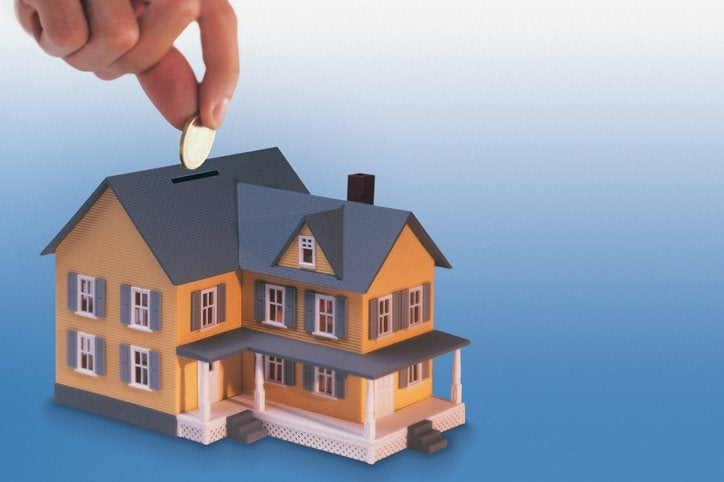 A hand drops money into a house-shaped coin bank