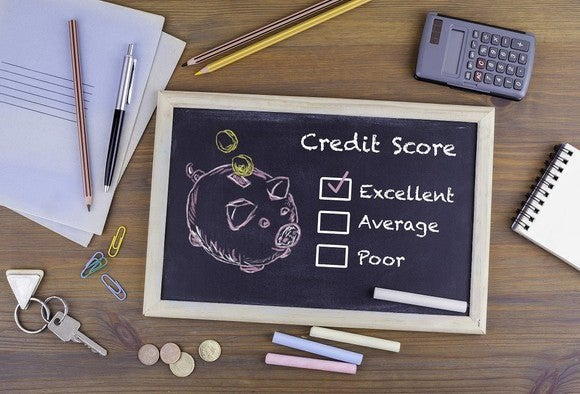 """On a desktop, surrounded by papers, pens, keys, coins, a calculator, and other items, is a small chalkboard. Drawn on the chalkboard is a picture of a piggy bank, next to the words """"credit score."""" Beneath that are written """"excellent,"""" """"average,"""" and """"poor,"""" with check boxes next to each. The box next to """"excellent"""" is checked."""