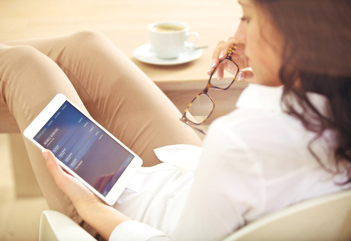 woman sitting looking at mobile bank accounts on tablet