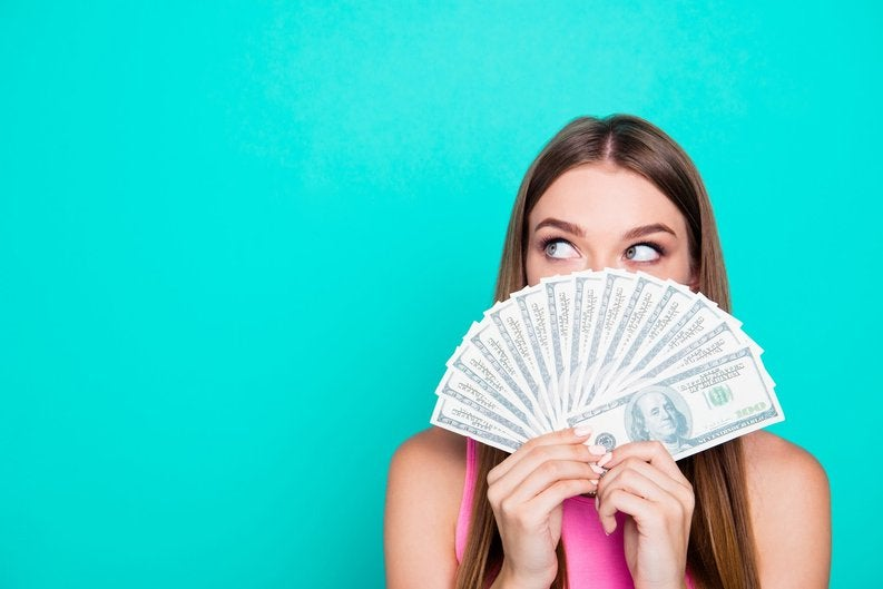 Young woman holding a fan of hundred-dollar bills in front of her face.