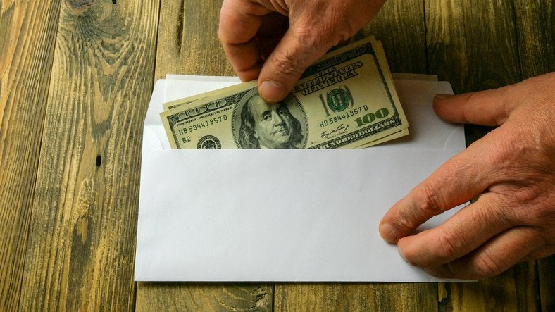 Someone places hundred-dollar bills into an envelope.