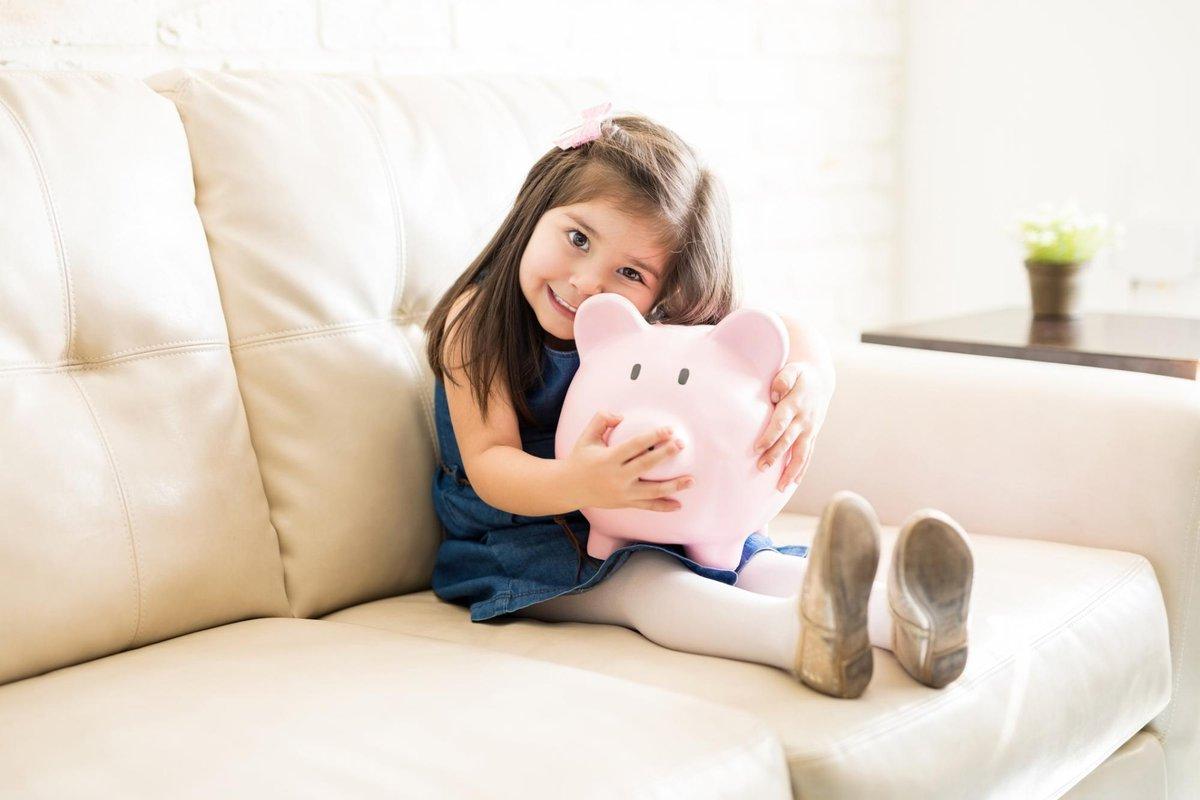 little girl clutching piggy bank