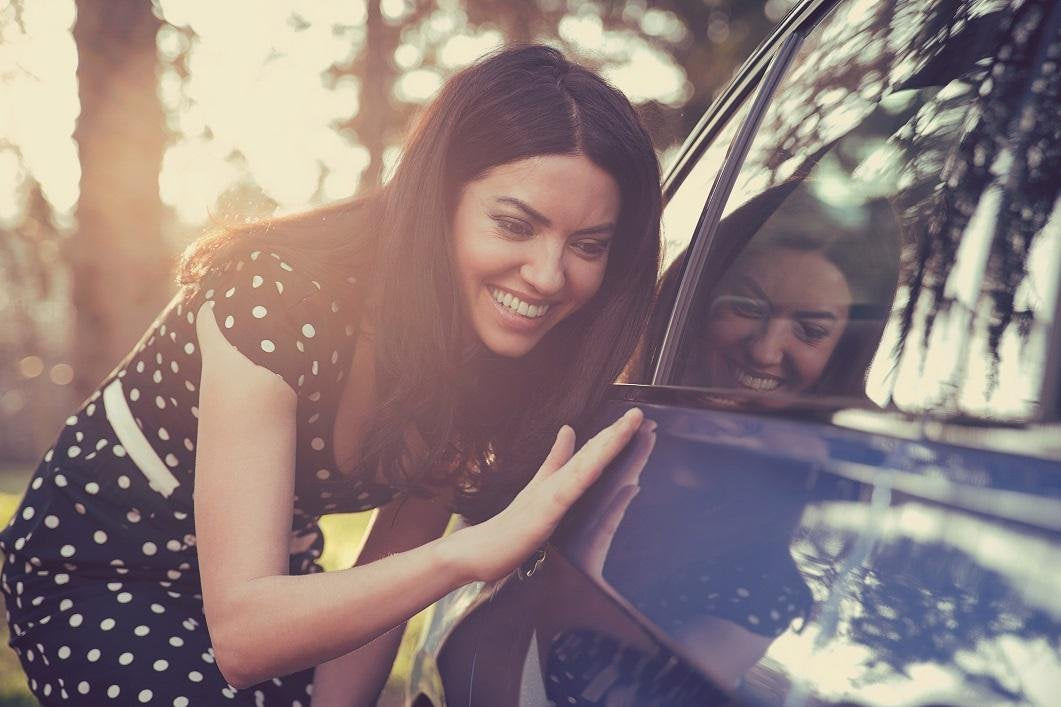 Young woman smiling as she inspects the exterior of a blue car.