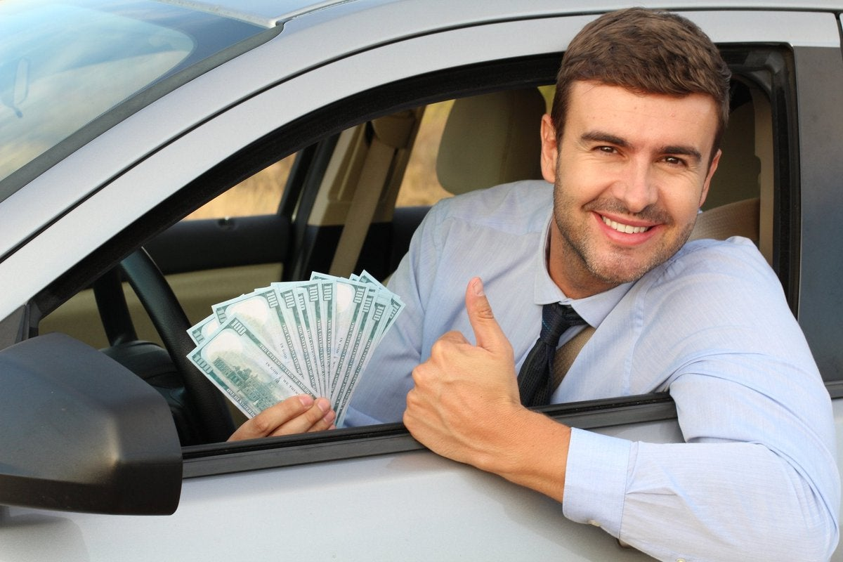 Driver leaning out of a car window holding hundred dollar bills.