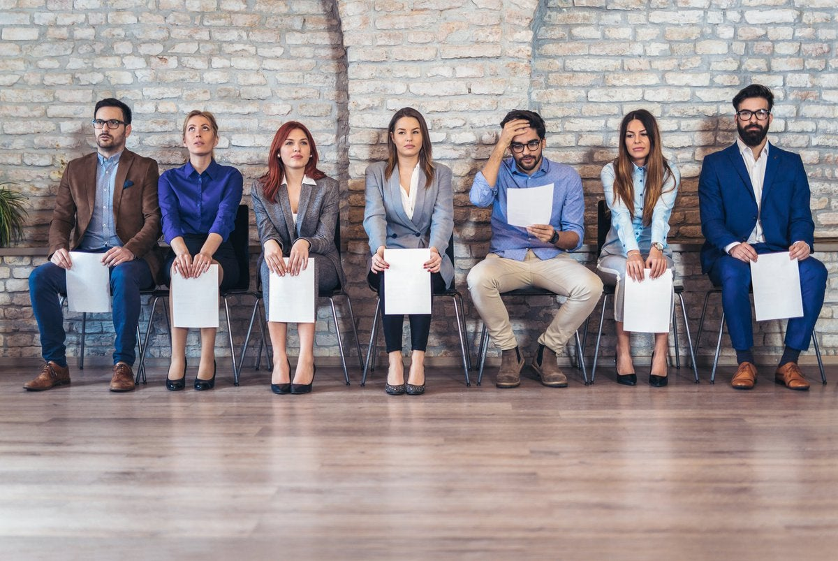 A line of people seated waiting for an interview with resumes in hand.