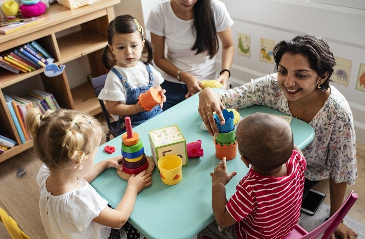A smiling teacher sitting at a table in her daycare classroom and playing with three young children.