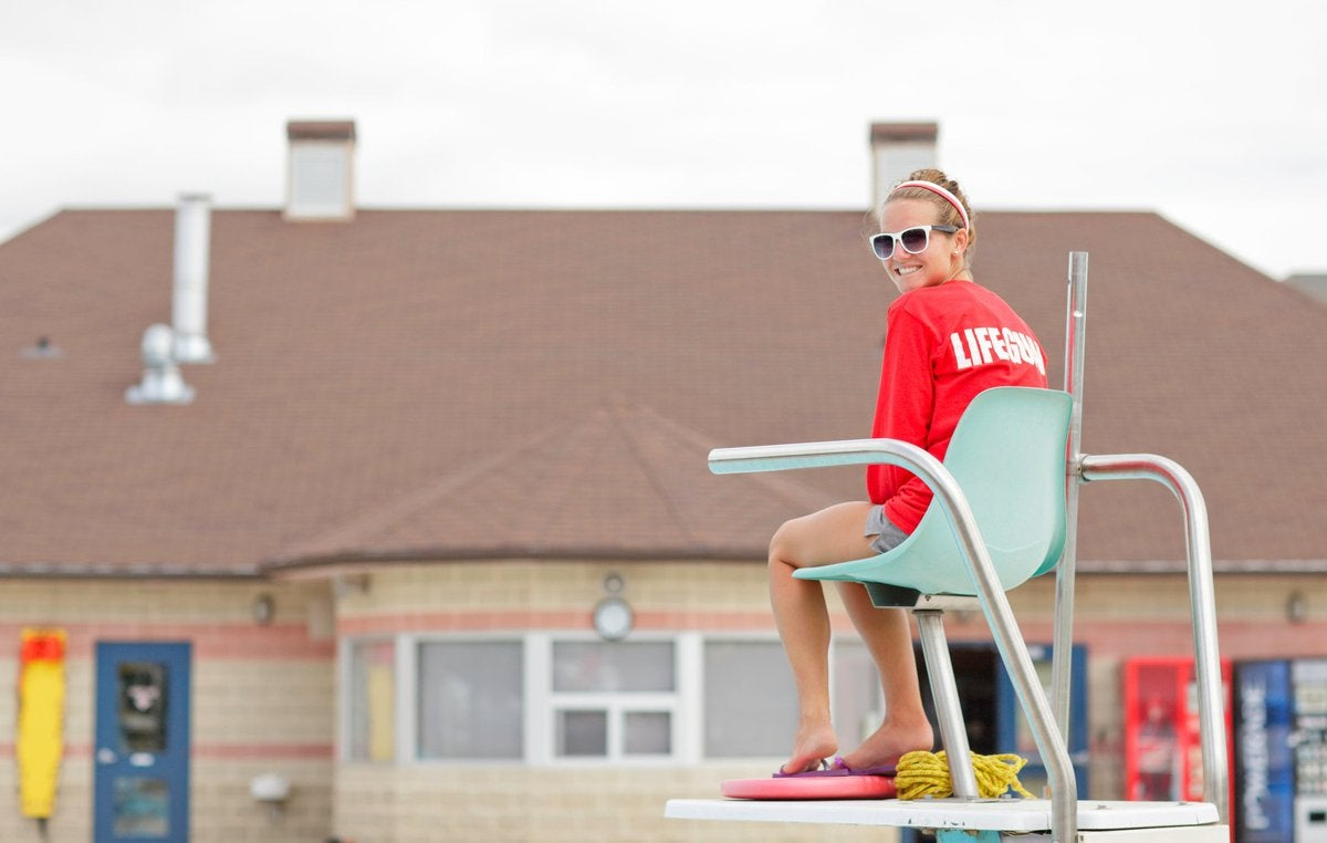 A smiling lifeguard sitting in a high chair with a building in the background.