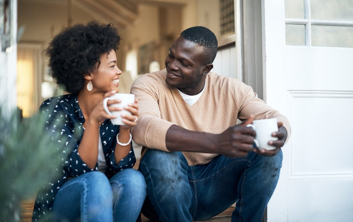 husband and wife sitting on porch drinking coffee