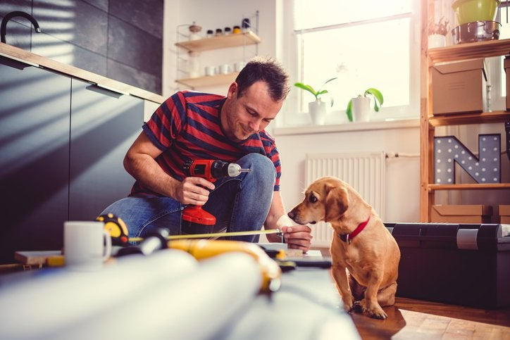 A man measuring new cabinets that he's installing in his kitchen while his dog sits next to him and watches.