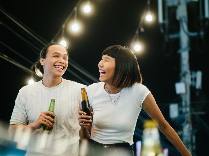 A laughing man and woman drinking beer while standing on a rooftop under string lights.