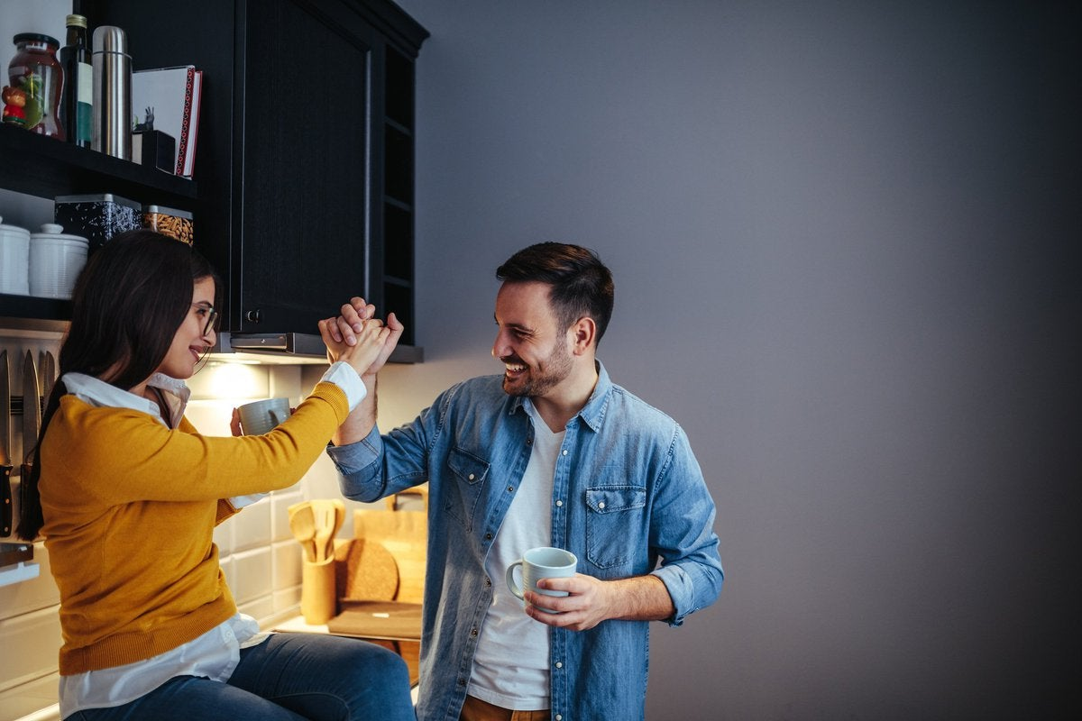 man and woman high five in a kitchen -- couple celebrating success goal