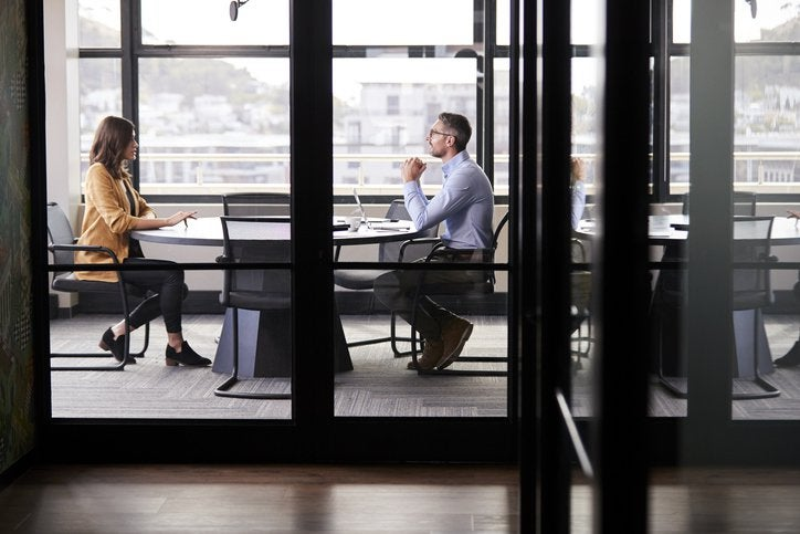 A man and woman sitting at opposite ends of a table in an office meeting room for a job interview.