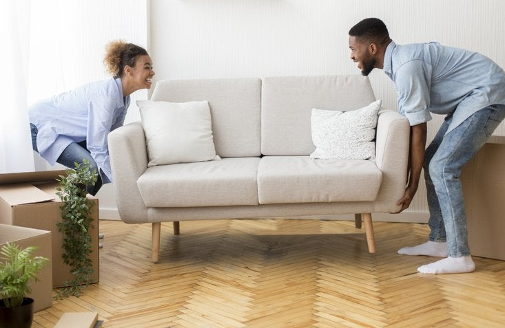A man and woman moving a new couch into their living room.