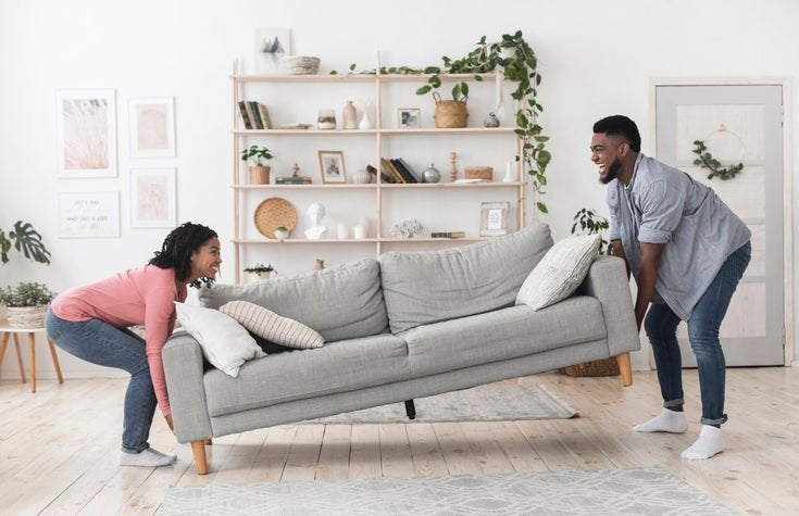 A smiling man and woman moving a couch into the living room in their new home.