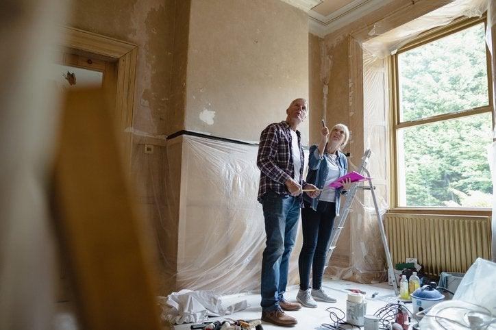 A man and woman looking around a room that's being renovated.