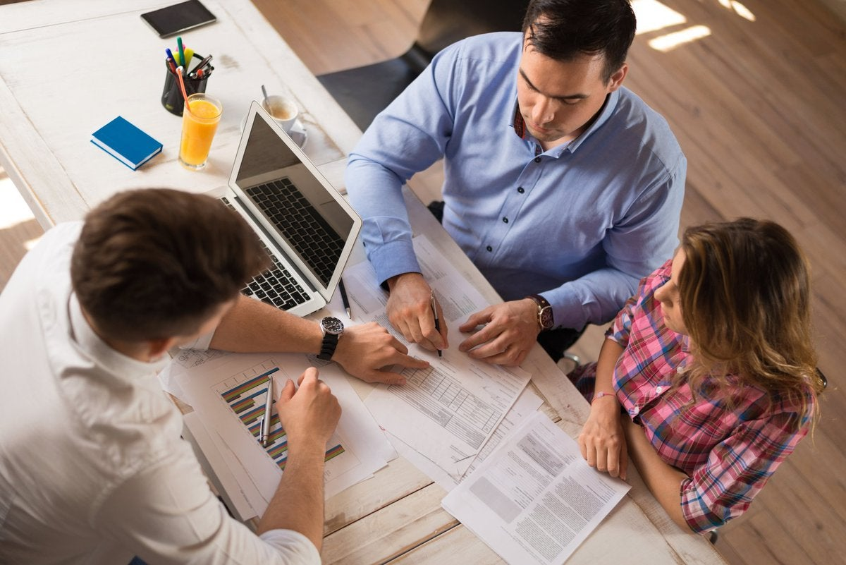 Banker reviewing financial paperwork with couple.