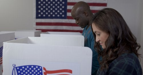A woman and man standing next to each other at two voting booths separated by dividers.