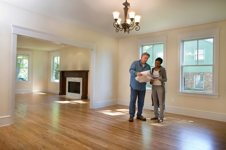 A man and woman standing in an empty living room and looking at blueprints of the house.