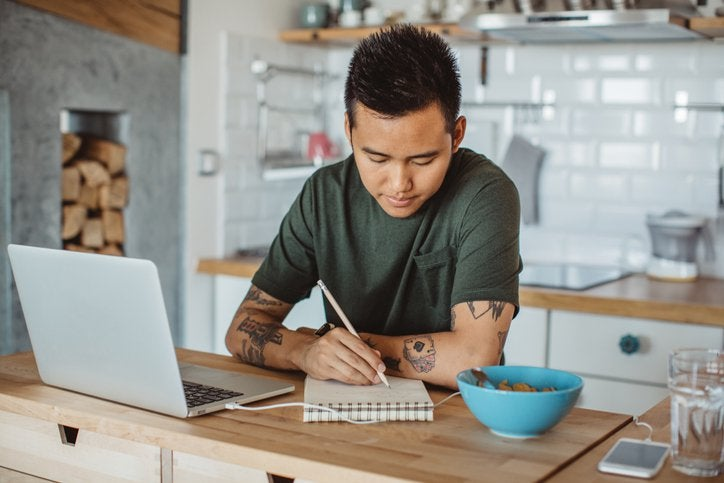 A man sitting at his kitchen table in front of an open laptop and writing in a notebook.