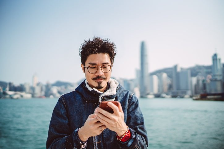A man looking at his phone while standing along a waterfront with a city skyline behind him.