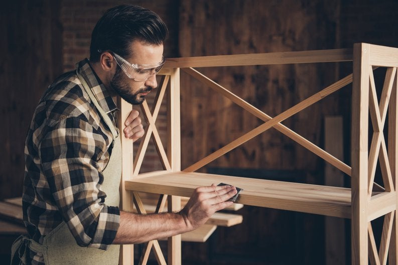A man building a piece of furniture out of wood in a workshop.